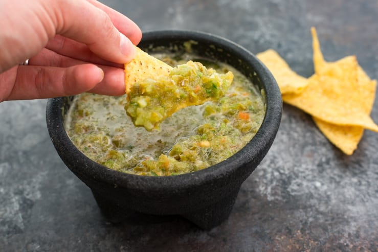 Texas Green Salsa being scooped with a chip