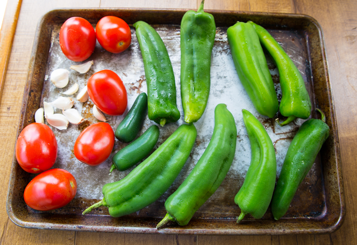 Chiles, tomatoes, and garlic, on a sheet pan about to be roasted for queso