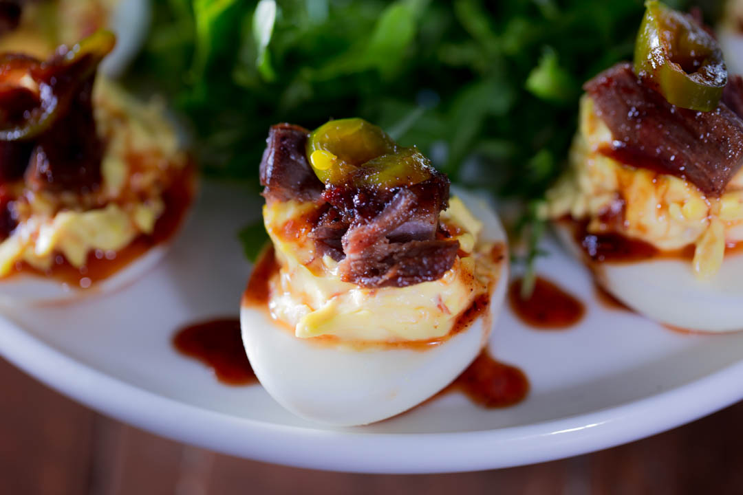 A close up of a brisket deviled egg with candied jalapeno
