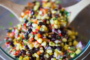 Corn and Black Bean Salad with Mexican Vinaigrette being tossed
