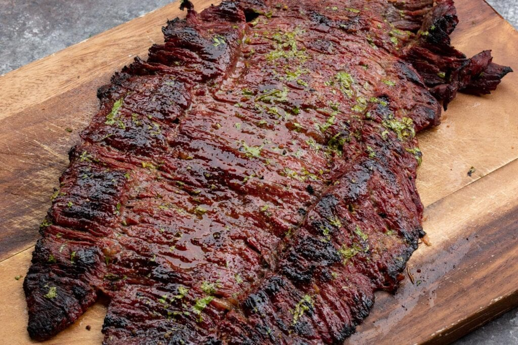 A slab of grilled Texas style skirt steak fajitas resting on a cutting board