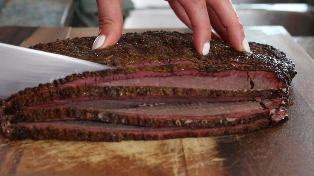 A photo of brisket being sliced for the brisket queso