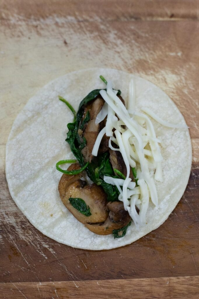 A corn tortilla with mushroom and spinach filling for making enchiladas