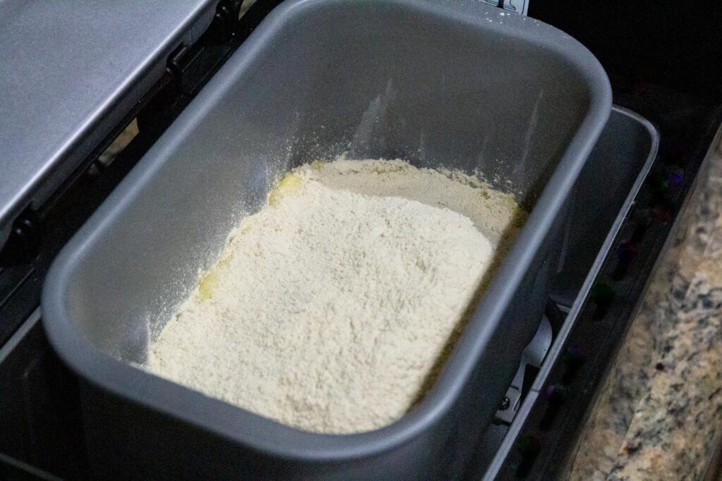 The bowl of the bread machine with all ingredients added
