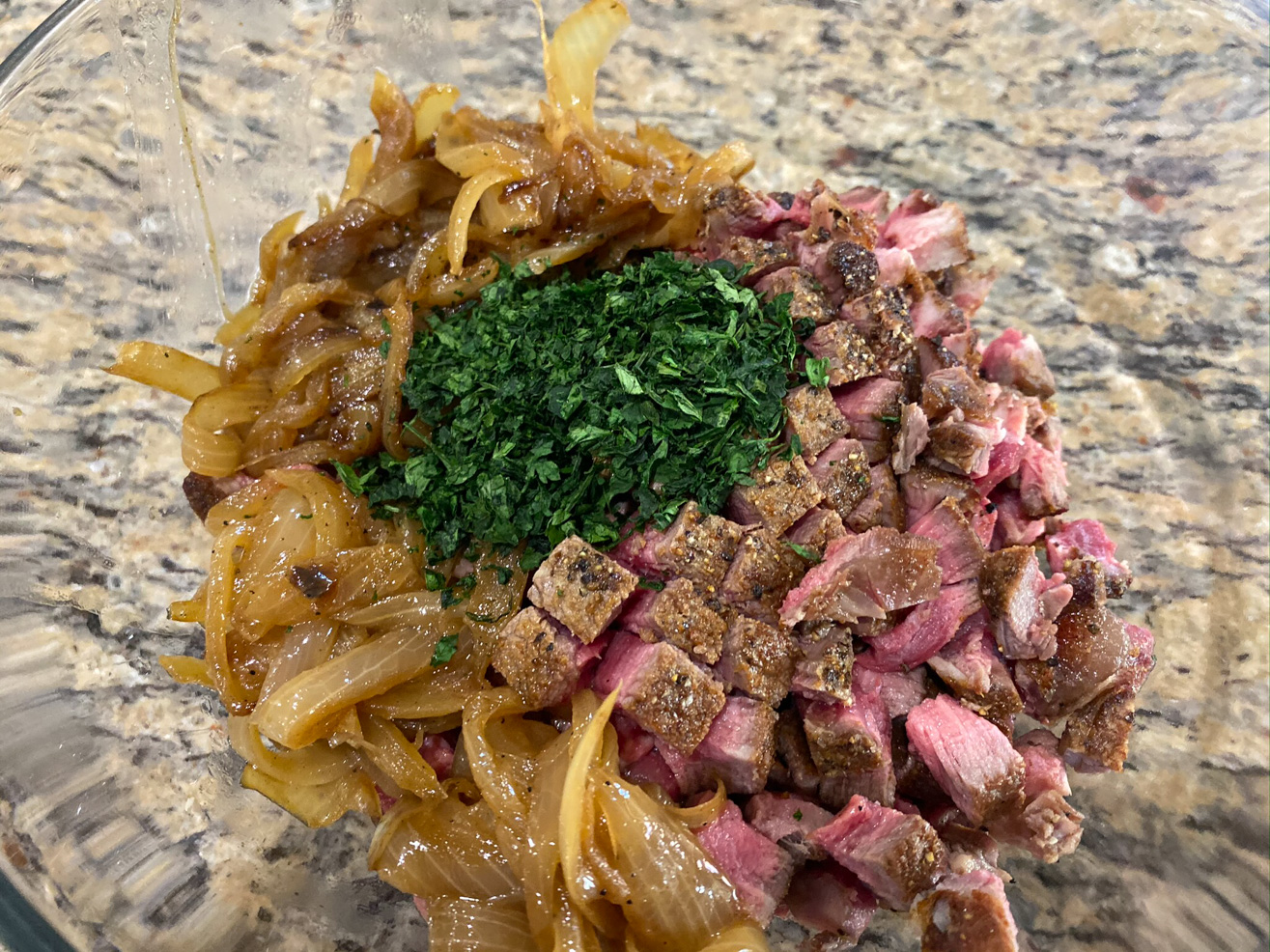 A bowl of seared filet mignon cubes, caramelized onion, and herbs