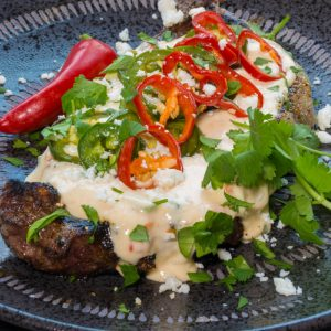 A steak covered with white queso and pickled jalapeno peppers