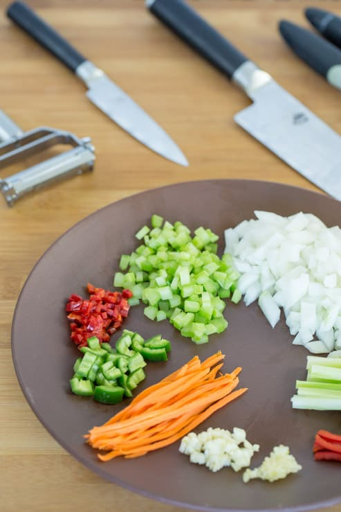 A colorful plate of vegetables chopped into diffferent knife cuts, and the knives used.