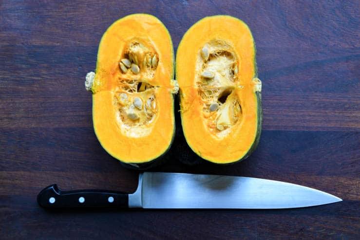 a kabocha squash cut in half by a wustoff chef knife
