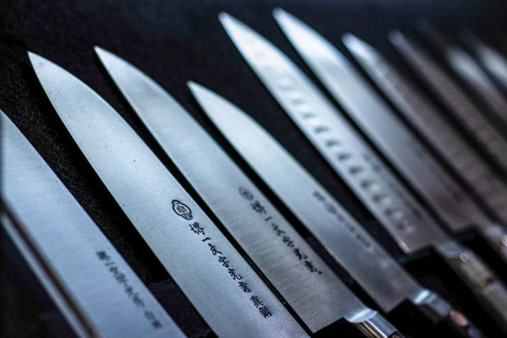 An array of Japanese knives with traditional lettering