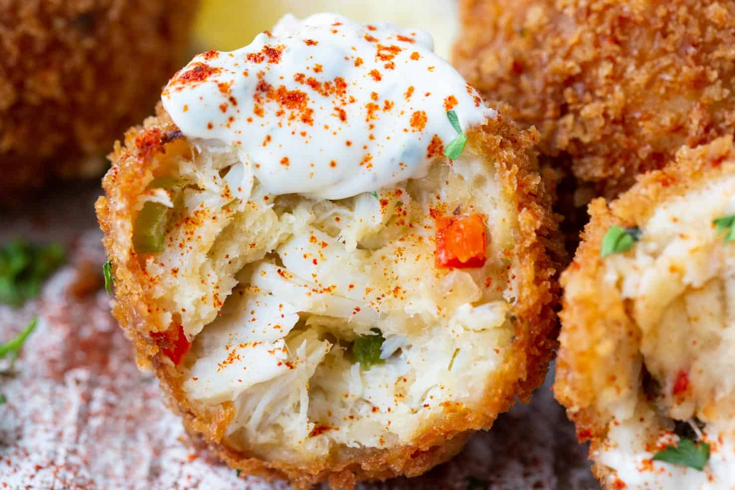 A fried crab ball, upclose dolloped with tartar.