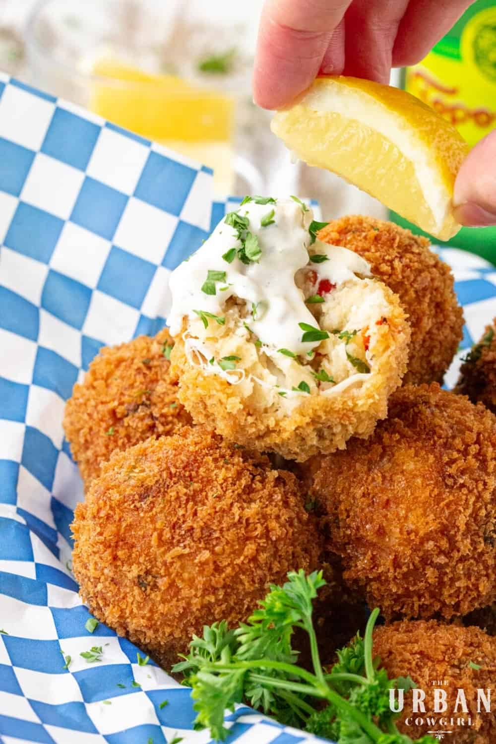 A basket of delicious golden brown fried crab balls being dunked in tartar sauce and spritzed with lemon.