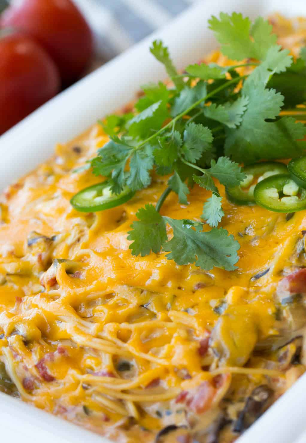 A completed cheesy chicken spaghetti casserole, baked and covered with cheese, topped with cilantro.