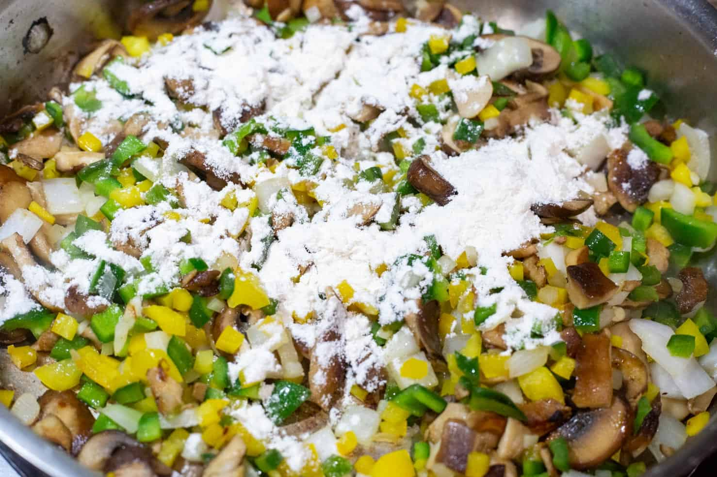 Sauteed poblano, yellow bell pepper, onion, and sprinkled with flour.