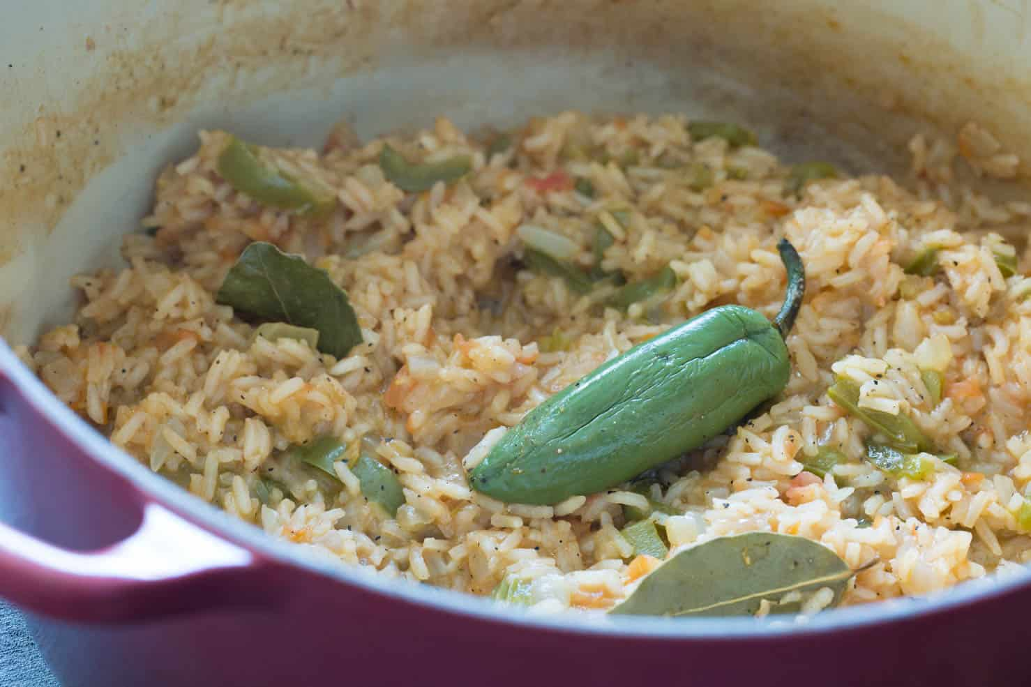 A roasted jalapeno atop mexican rice in a bowl.