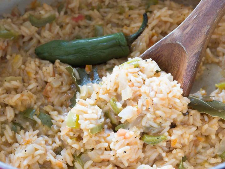 A wooden spoonful full of fluffy mexican rice with peppers.