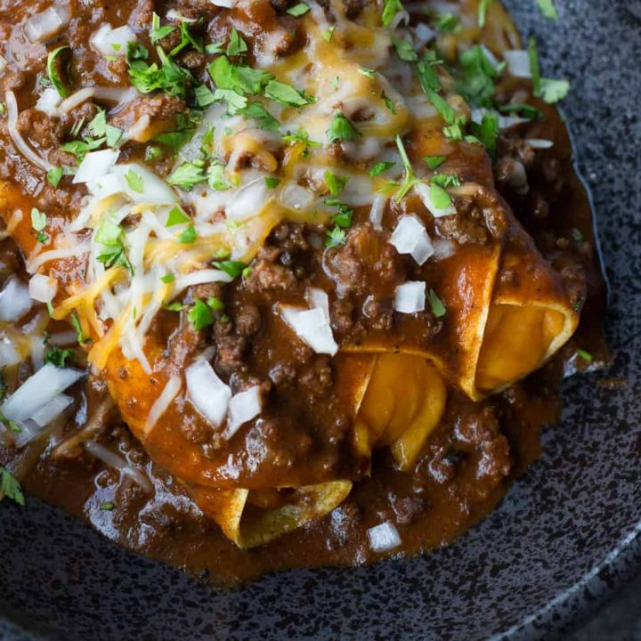 Cheese enchiladas on a black plate topped with chili gravy