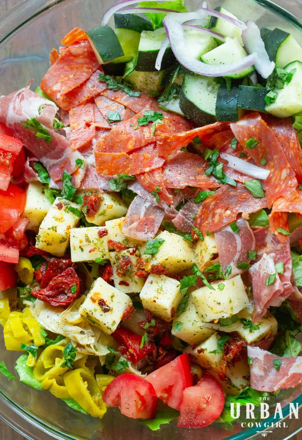 A bright bowl of antipasto salad, marinated cheese, candied tomatoes, cured meats, and bright peppers.