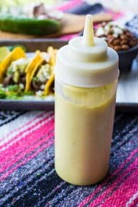 A squeeze bottle of creamy jalapeno sauce standing in front of a plate of tacos.