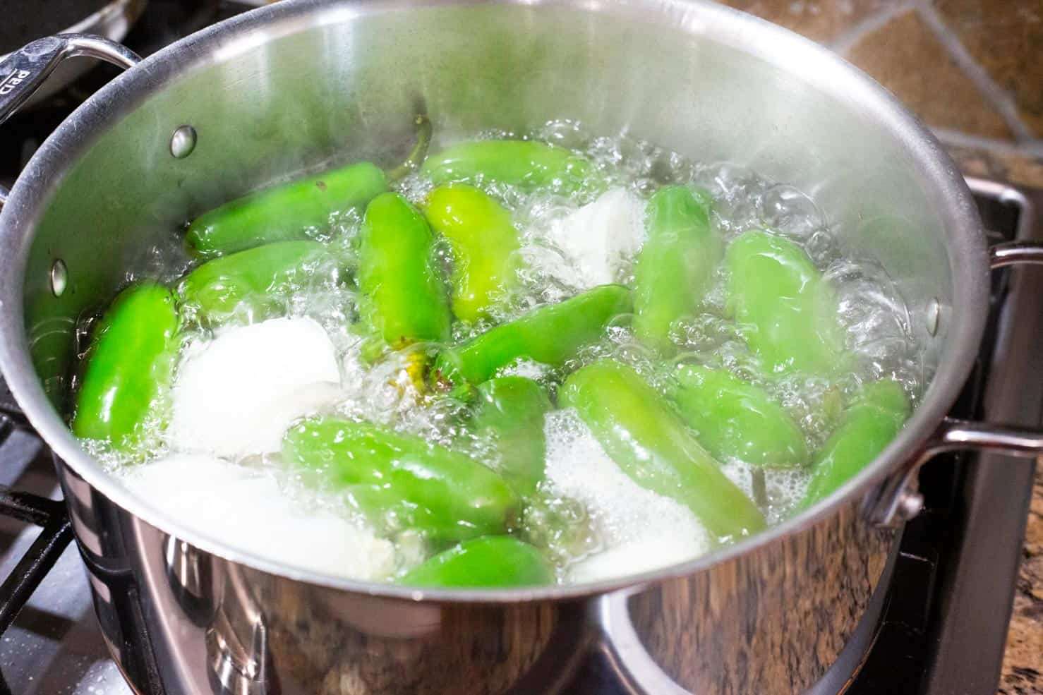 jalapenos and onion in the water bath being boiled on a stove