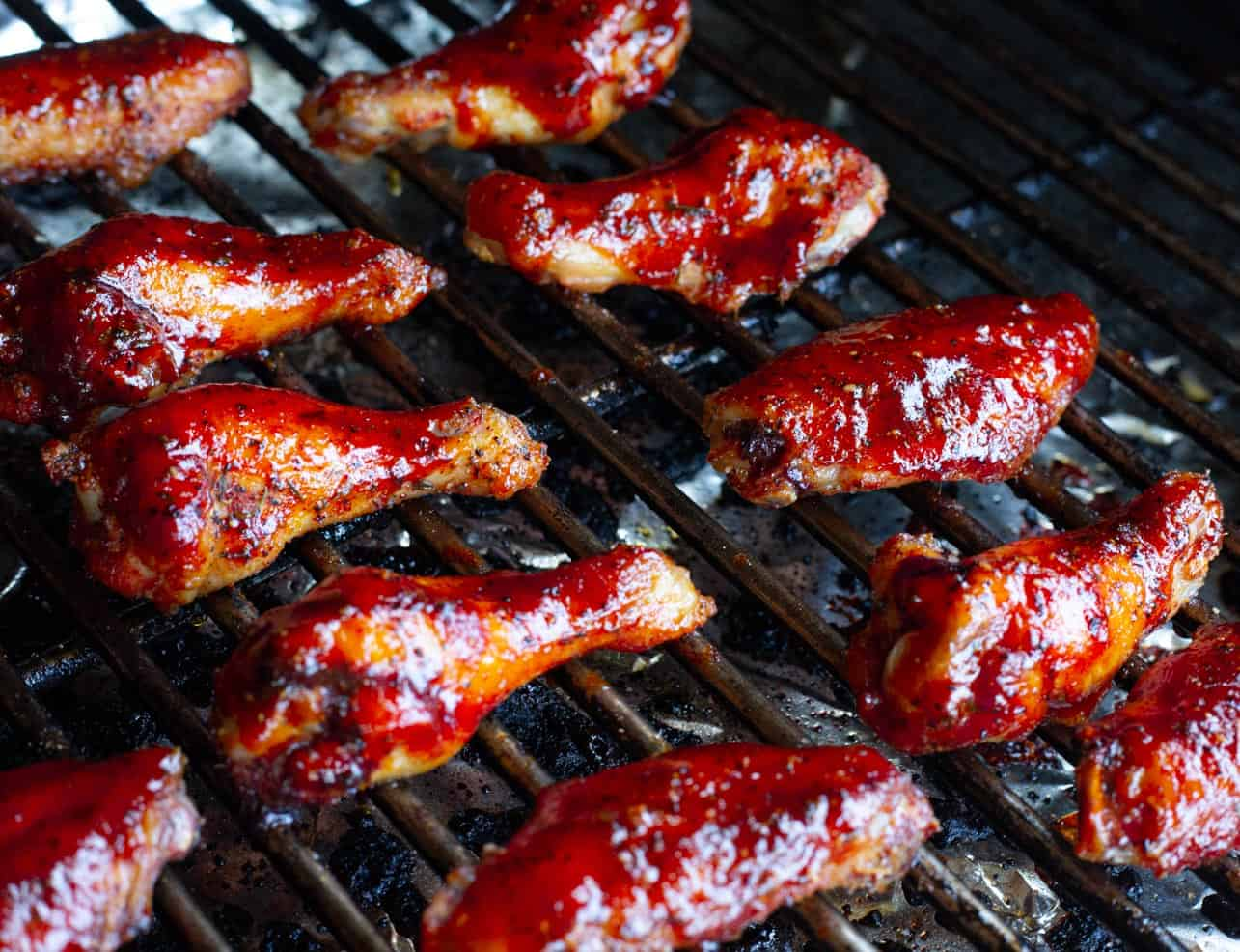 Wings on a barbecue smoker coated with strawberry barbecue sauce