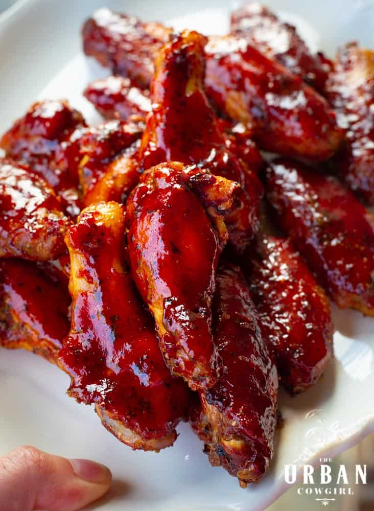 A generous heap of strawberry barbecue wings on a white plate.