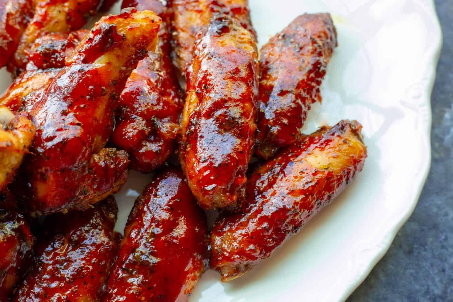 A plate containing smoked chicken wings with a shiny strawberry barbecue sauce.