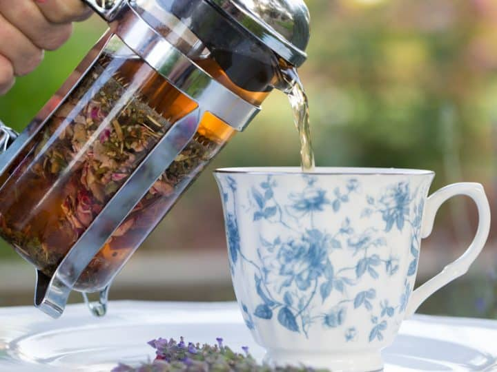 A beautiful floral tea cup being poured into from a french press filled with tea.
