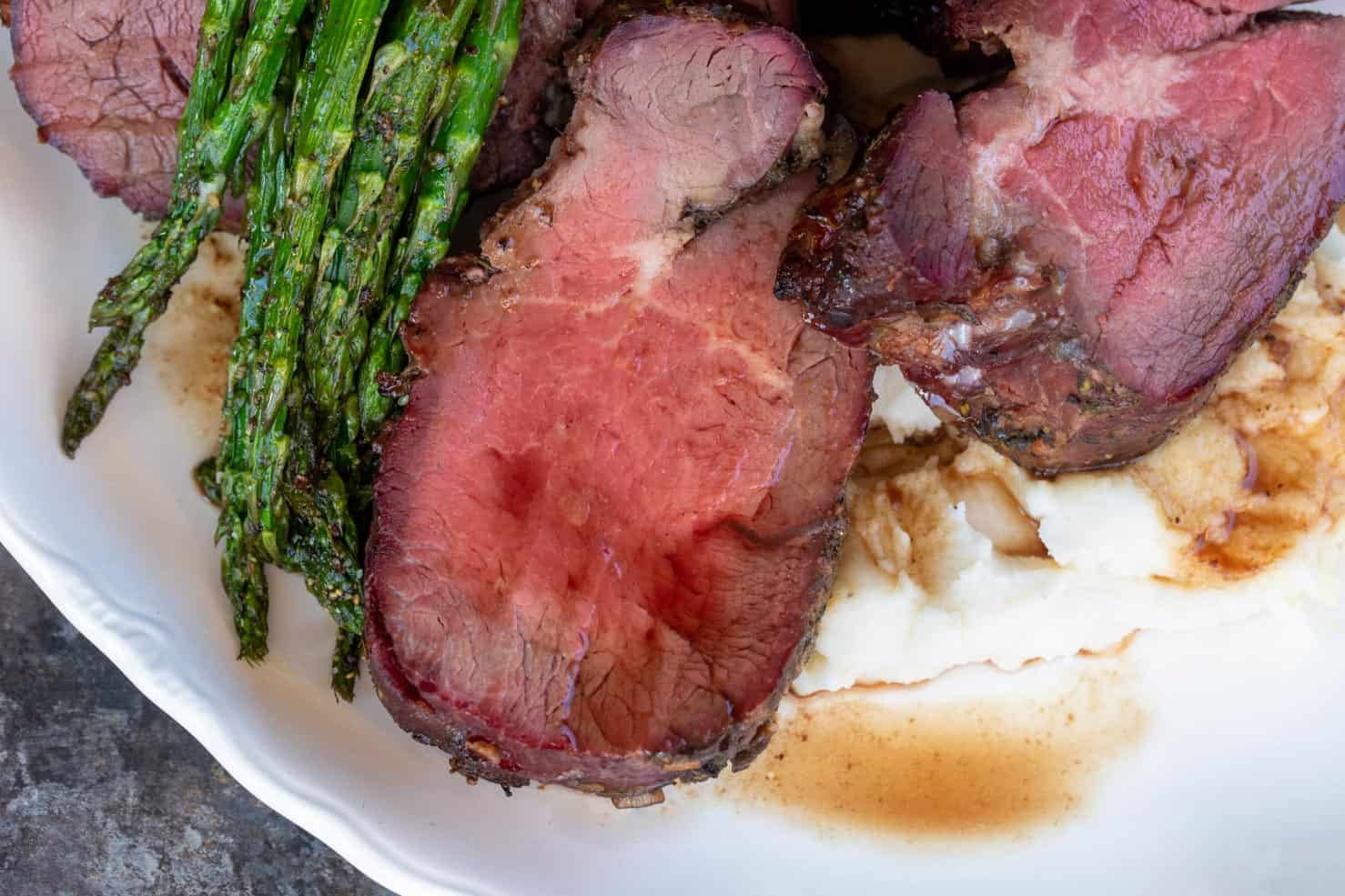 A white plate filled with mashed potatoes, sliced of pink and juicy smoked beef tenderloin medallions, and roasted asparagus.