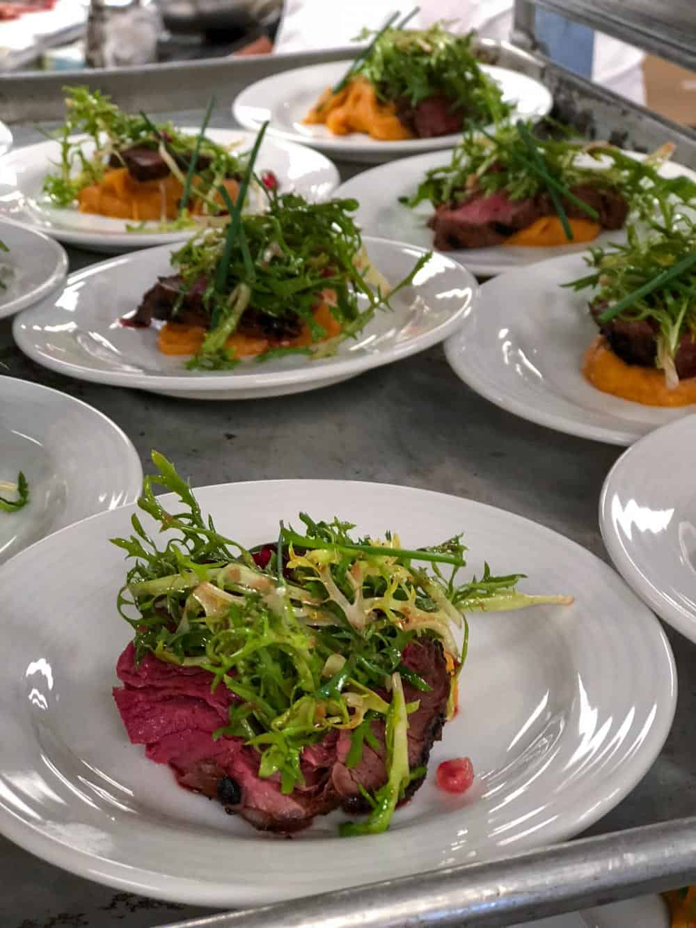 A close up of the beef tenderloin atop sweet potato puree ready to be served to guests.
