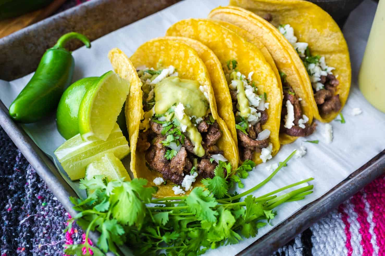 A pan of steak street tacos covered in a creamy jalapeno sauce