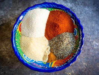 A colorful mexican bowl full of the spices to make our carne asada seasoning blend