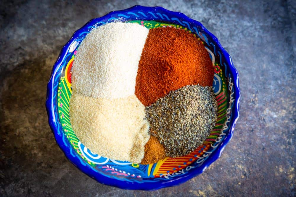 A colorful bowl filled with 5 different bright spices.