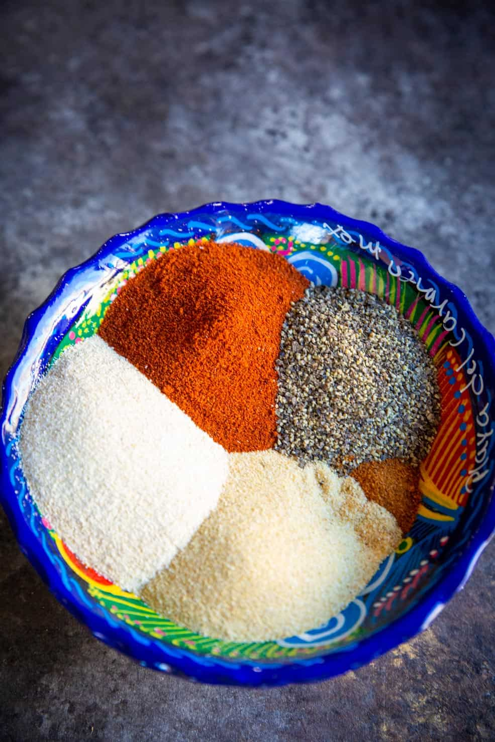 A close up of chili powder and various other spices which commonly go in carne asada seasoning.