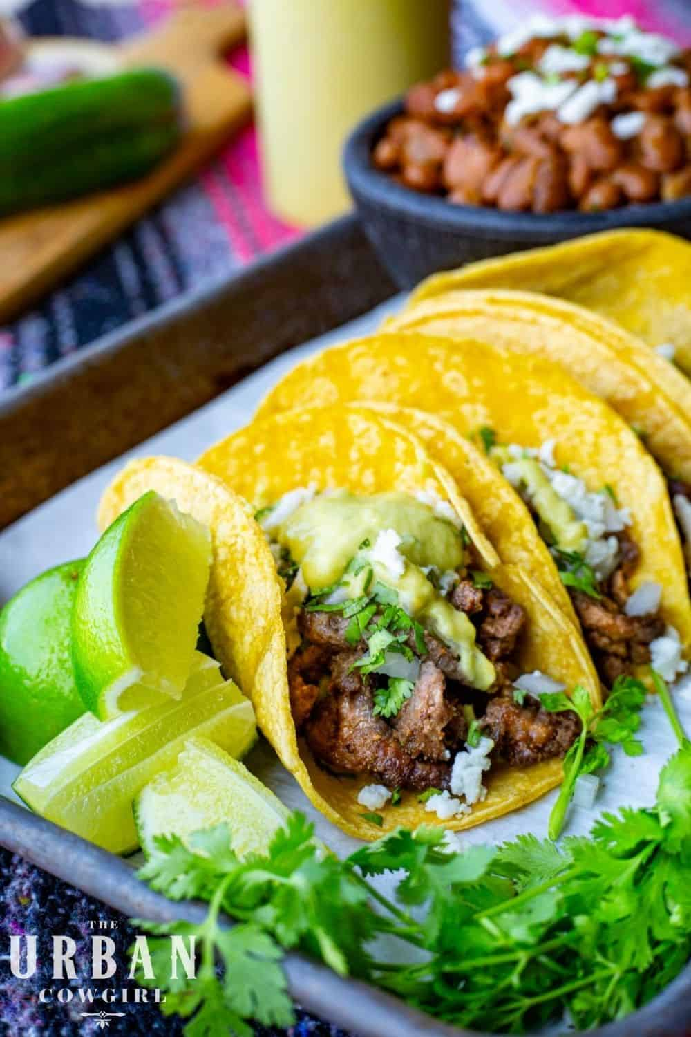 A pan of steak street tacos covered in a creamy jalapeno sauce - close up