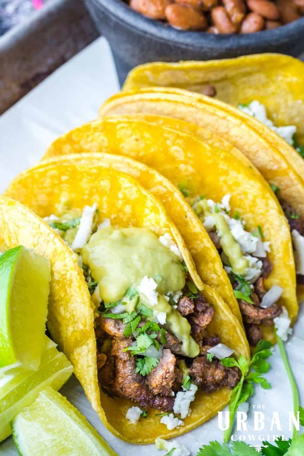 A pan of steak street tacos covered in a creamy jalapeno sauce with cheese and limes
