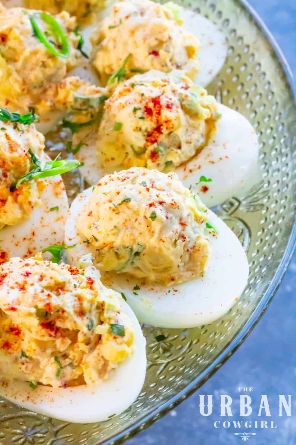A long, large platter of cajun deviled eggs sprinkled with herbs.