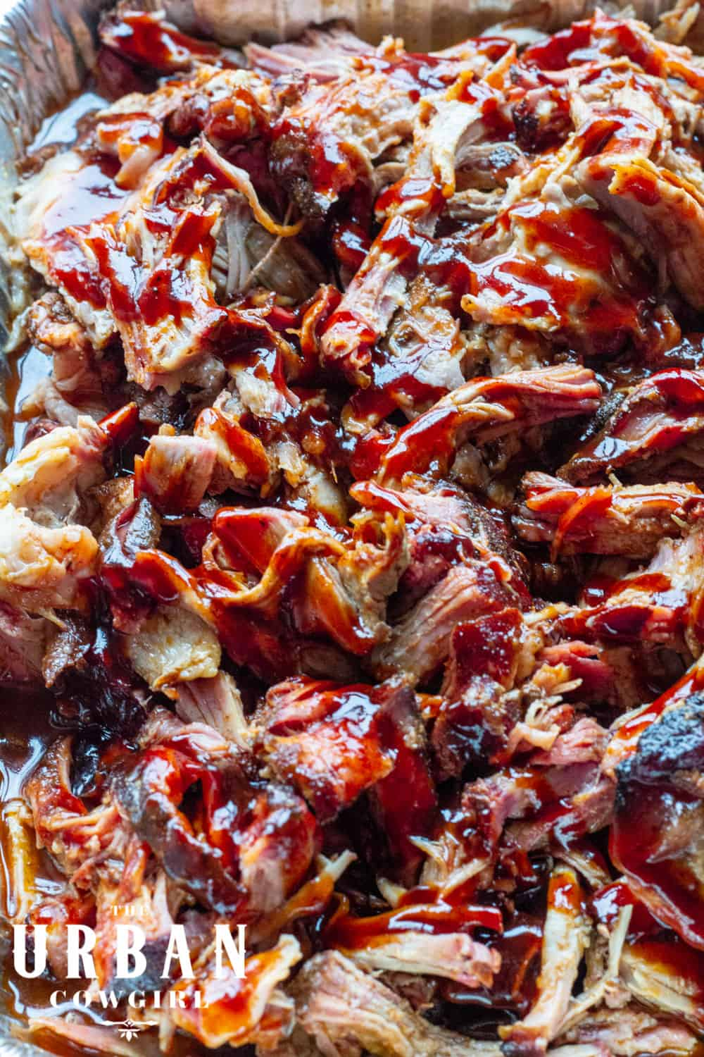 A close up tray of juicy pulled pork with shiny barbecue sauce made on the pellet grill.