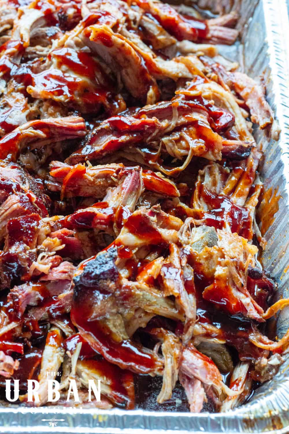 A close up tray of juicy pulled pork with red barbecue sauce.