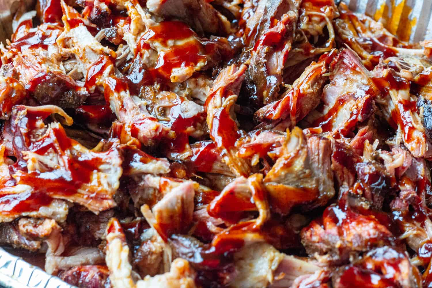 A close up tray of juicy pulled pork with shiny barbecue sauce.