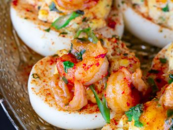 A close up of loaded crawfish deviled eggs on a silver platter.