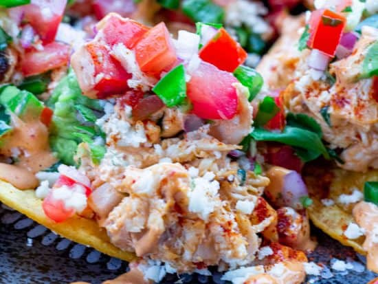 smoked chicken nachos appetizer laid out on a black plate