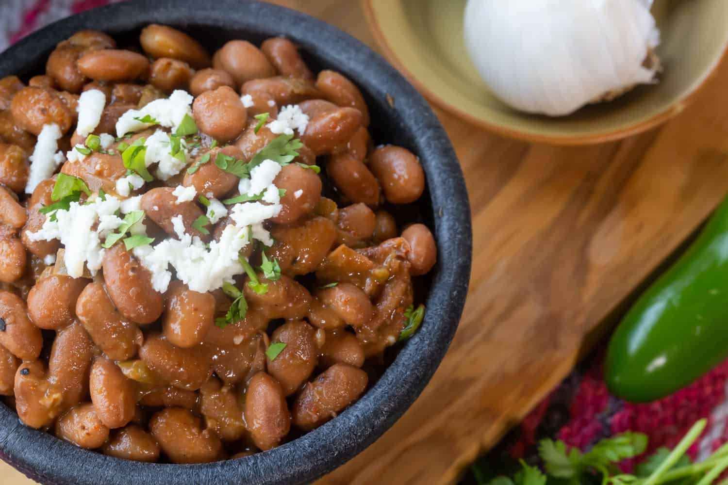 A bowl of glistening cooked pinto beans topped with cilantro and crema.