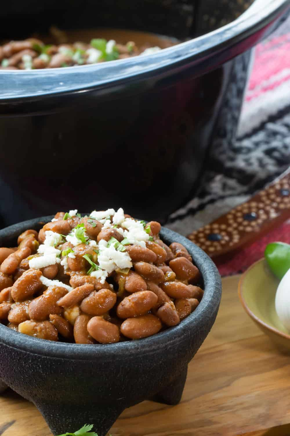 A close up of a cup of beans, topped with garnishes, served in front of a crockpot.