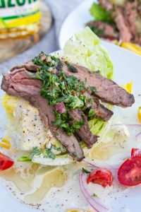 A wedge salad crowned with grilled skirt steak and green chimichurri sauce