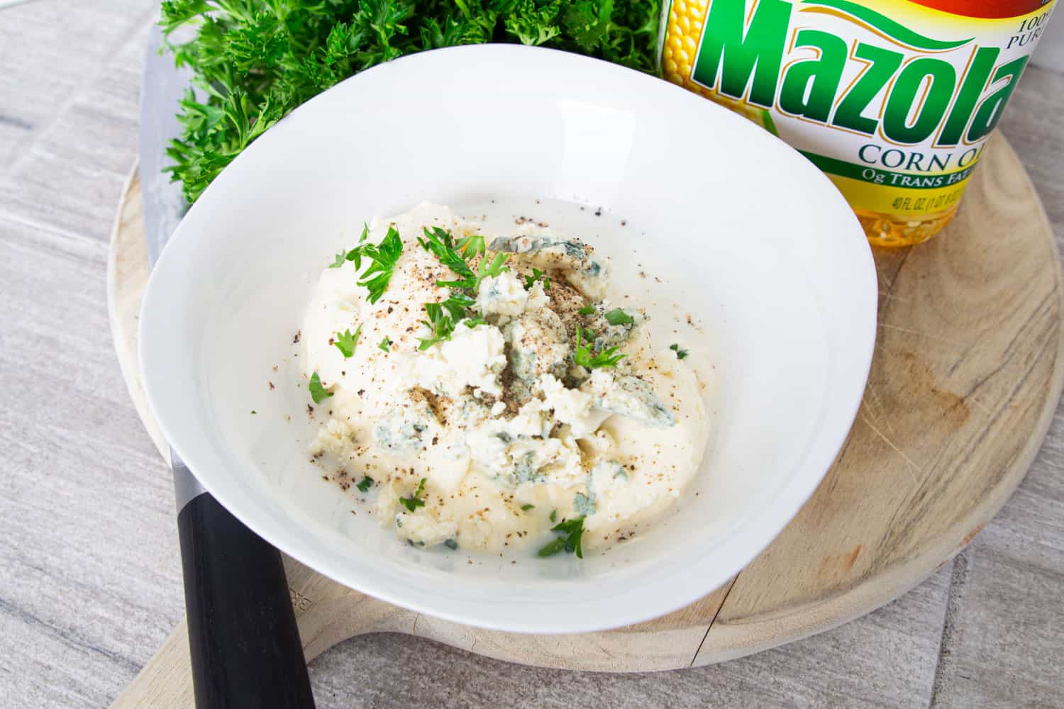 A bowl of homemade blue cheese dressing ingredients: mayonnaise, blue cheese, garlic, milk, and fresh herbs
