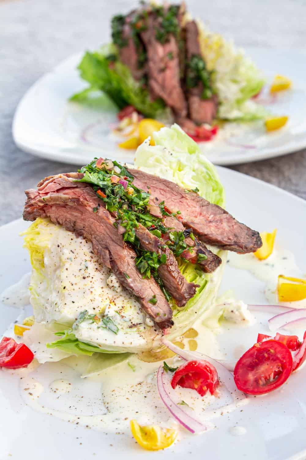 A wedge salad topped with chimichurri skirt steak in front of the ocean