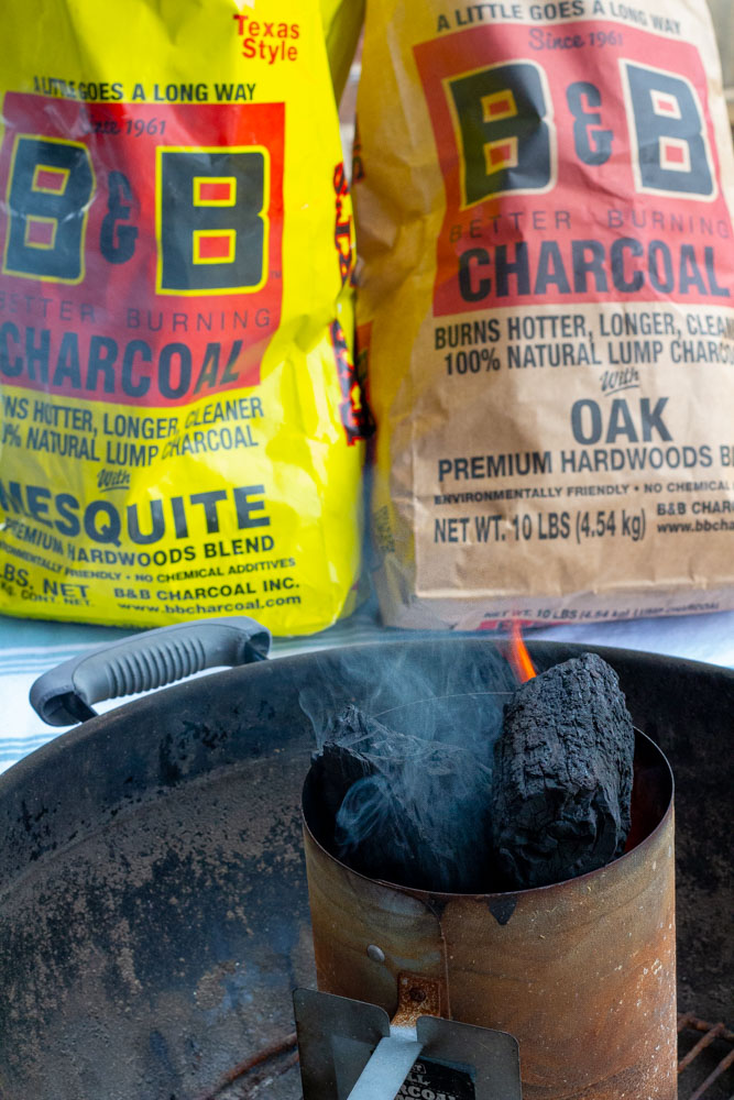 A charcoal grill with a charcoal chimney beginning to smoke.