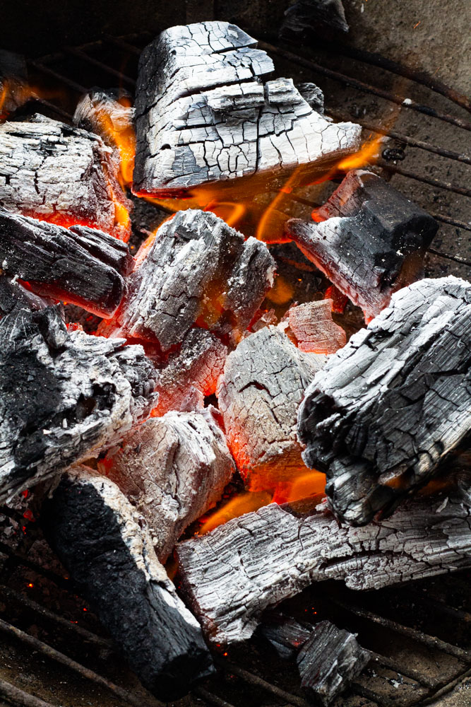 A close up of charcoal properly graying and almost ready to cook.