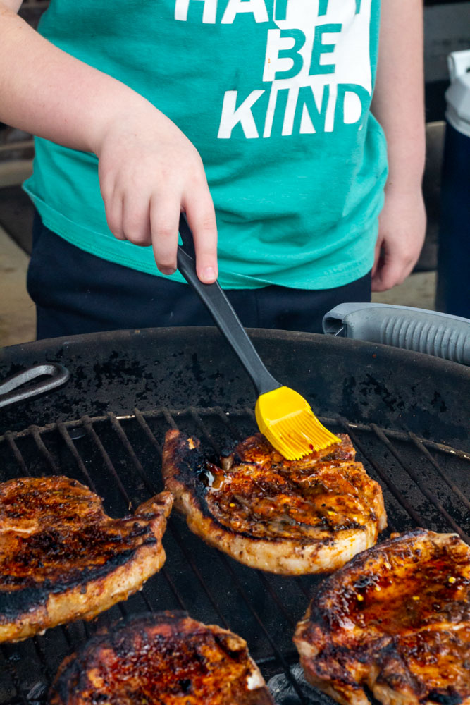 My little boy standing in front of the grill glazing the pork chops with hot honey.