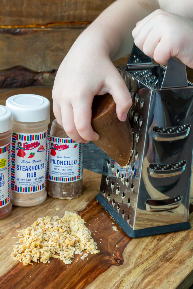 A child's hands grating fresh piloncillo brown sugar from the cone on a kitchen grater, an important step in preparing the pork rub.
